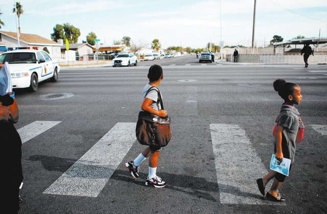 Shariya (cq) Hooks, 9, and Nakiah (cq) Hooks, 7, cross Balzar Avenue at Martin Luther King Boulevard on Monday, Nov. 18, 2013. (Samantha Clemens/Las Vegas Review-Journal)