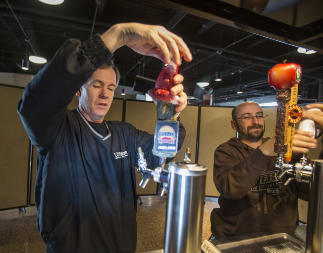 Thomas & Mack Food and Beverage Director Joe Carter, left, and Concession Manager Shawn Corr set up taps at the arena's craft beer kiosk.  (Jeff Scheid/Las Vegas Review-Journal)