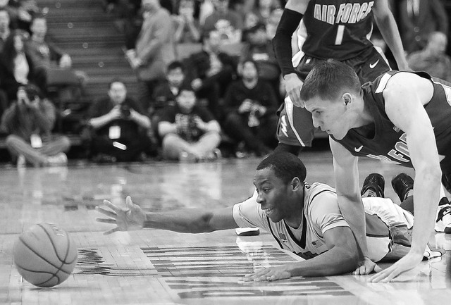 UNLV's Kevin Olekaibe (3) dives for a lose ball against the Air Force Academy's Marek Olesinski (0) during their basketball game at the Thomas & Mack Center in Las Vegas on Jan. 4, 2014. (Jason Be ...