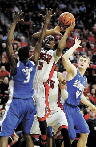 UNLV's Kevin Olekaibe (3) shoots over the Air Force Academy's Justin Hammonds (3) and Chase Kammerer (44) during their basketball game at the Thomas & Mack Center in Las Vegas on Jan. 4, 2014. (Ja ...