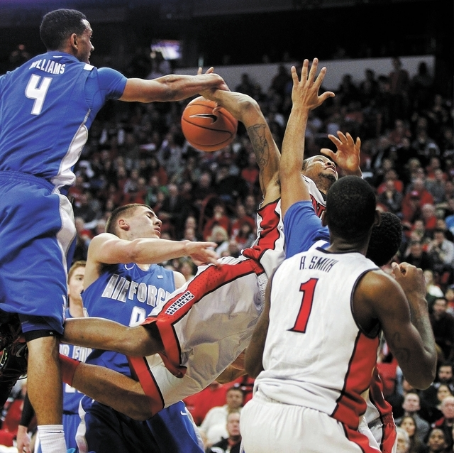 UNLV's Bryce Dejean-Jones (13) gets fouled by the Air Force Academy's Kamryn Williams (4) during their basketball game at the Thomas & Mack Center in Las Vegas on Jan. 4, 2014. (Jason Bean/Las Veg ...
