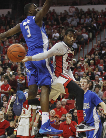 UNLV's Deville Smith (33) passes the ball around the Air Force Academy's Justin Hammonds (3) during their basketball game at the Thomas & Mack Center in Las Vegas on Jan. 4, 2014. (Jason Bean/Las  ...