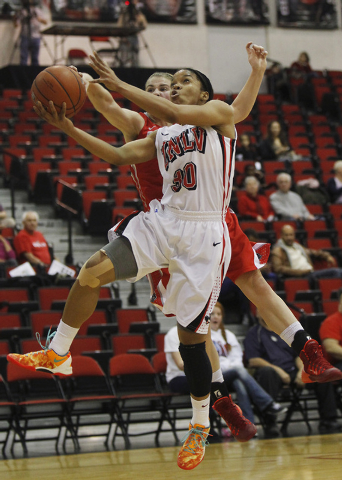 UNLV's Mia Bell (30) drives past New Mexico's Brooke Allemand (1) for a layup in Wednesday's 78-56 Mountain West victory at Cox Pavilion. Bell finished with nine points, 10 assists and three ...