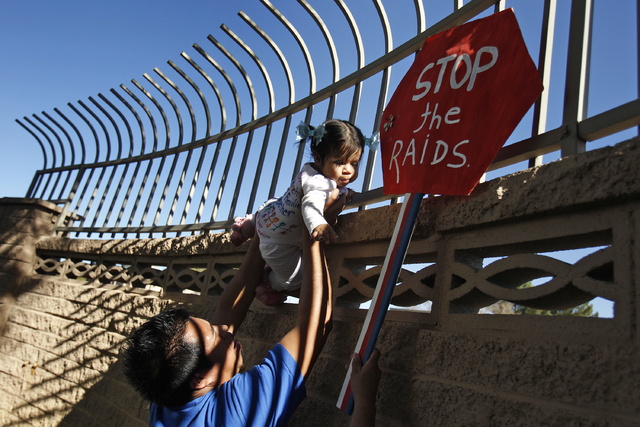 Alejandro Estrada holds up his 1-year-old daughter, Ruby Esmeralda Estrada, during a protest outside of a fundraiser for U.S. Rep. Joe Heck, R-Nev., on Friday in Las Vegas. House Speaker John Boeh ...