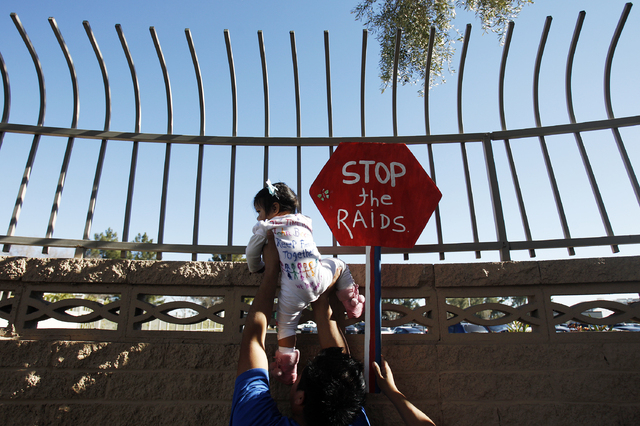 Alejandro Estrada holds up his 1-year-old daughter, Ruby Esmeralda Estrada, during a protest outside of a fundraiser for U.S. Rep. Joe Heck, R-Nev., in Las Vegas on Friday. (John Locher/Las Vegas  ...