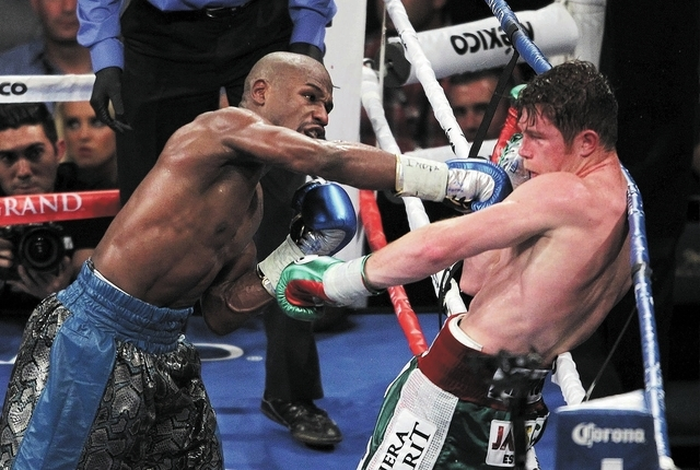 Floyd Mayweather, left, lands a blow against Canelo Alvarez for the WBC and the WBA Super Welterweight titles at the MGM Grand Garden Arena in Las Vegas on Sept. 14, 2013. (Jason Bean/Las Vegas Re ...