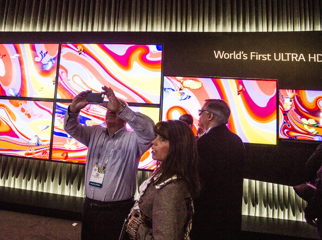 People stand beside the LG Ultra HD at the Las Vegas  Convention Center on Tuesday, Jan. 7, 2014. The annual electronic show features the latest in consumer technology started  Tuesday. Over 150,0 ...