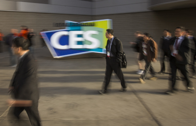 People walk pass the CES sign at the Las Vegas  Convention Center on Tuesday, Jan. 7, 2014. The annual electronic show features the latest in consumer technology started  Tuesday. Over 150,000 are ...