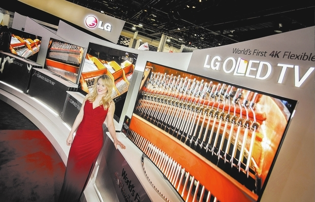 A model stands in front of LG's flexible 4K OLED TV's at the Las Vegas  Convention Center on Tuesday, Jan. 7, 2014. The annual electronic show features the latest in consumer technology started  T ...