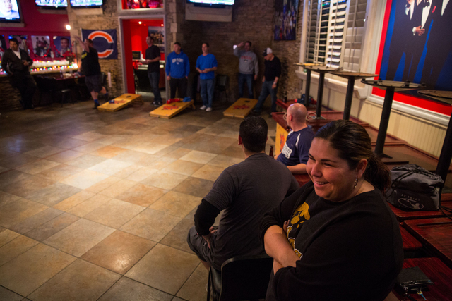 Kristy Hingtgen, bottom right, watches as fellow cornhole enthusiasts play at the Double Yoke, located at 6050 Sky Pointe Drive, Thursday, Jan. 2, 2014. (Samantha Clemens/View)