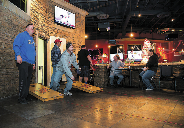 K.T. Thomas, left, and Mike Otte, second from left, practice throwing their bean bags before playing cornhole at the Double Yoke, located at 6050 Sky Pointe Drive, Thursday, Jan. 2, 2014. The bean ...