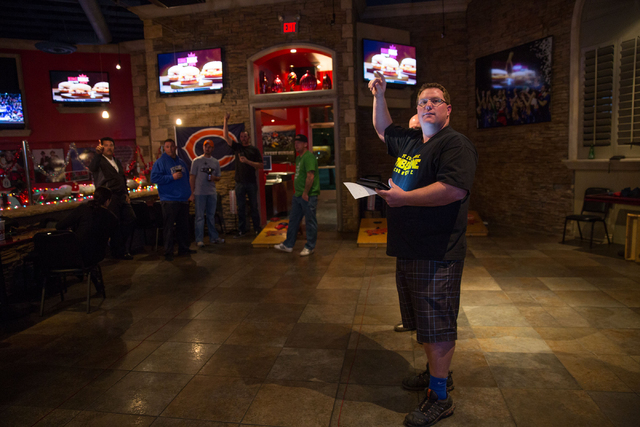Damon Cochran calls out who is playing with who before starting rounds of cornhole at the Double Yoke, located at 6050 Sky Pointe Drive, Thursday, Jan. 2, 2014. A group of cornhole enthusiasts are ...
