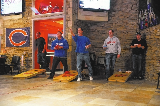 A group of cornhole enthusiasts meet and play at the Double Yoke, located at 6050 Sky Pointe Drive, Thursday, Jan. 2, 2014. The bean bag tossing lawn game is won when a player reaches 21 points af ...