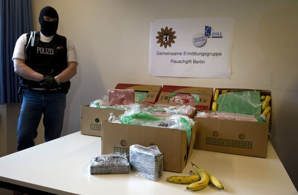 A masked policeman stands next to banana crates with confiscated drugs in the police headquarters in Berlin, Tuesday Jan.7, 2014. Poster in center reads : Special Drug Investigation Group Berlin.  ...