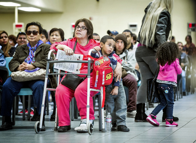 Ramiro Mendoza, 5, leans against Graciel Renteria while she waits to gets and ID  at the Department of Motor Vehicles office, 2701 E. Sahara Avenue on Friday, Jan. 17, 2014. The DMV conducts facia ...