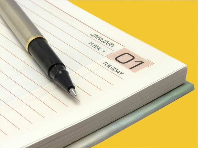 A image showing first January on a diary with pen on isolated color background with fine clipping path.