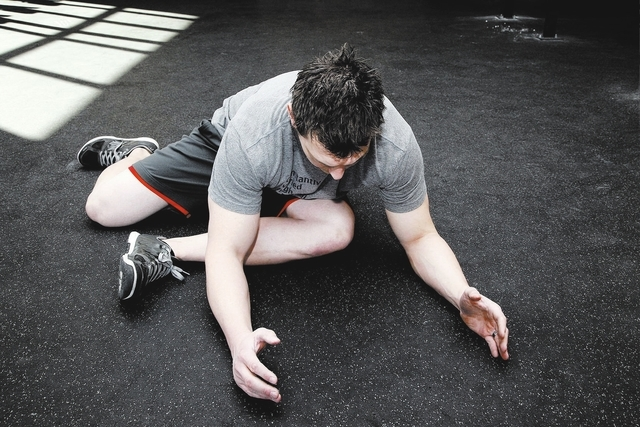 Trainer Chris Huth demonstrates the finishing position for the glute stretching method. (Justin Yurkanin/Las Vegas Review-Journal)