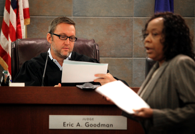 Justice of the Peace Eric Goodman views a motion filed by attorney Alzora Jackson, right, representing murder  suspect Nathan Burkett,  during a preliminary hearing Thursday, Aug. 16, 2012 in Las  ...