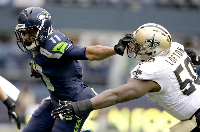 Seattle Seahawks wide receiver Percy Harvin, left, fends off New Orleans Saints middle linebacker Curtis Lofton (50) during the first half of an NFC divisional playoff NFL football game in Seattle ...