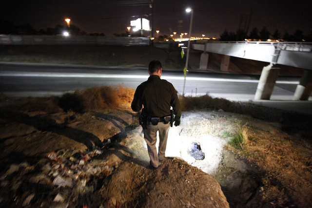 Las Vegas Police officer Ty Muncie walks down an embankment after searching for homeless people during the Southern Nevada Homeless Census urban count in Las Vegas on Wednesday. (Justin Yurkanin/  ...