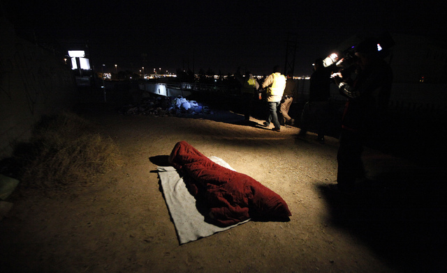 A homelessperson bundles up while sleeping on top of a steep embankment as volunteers make a count during the Southern Nevada Homeless Census urban count in Las Vegas on Wednesday. (Justin Yurkani ...