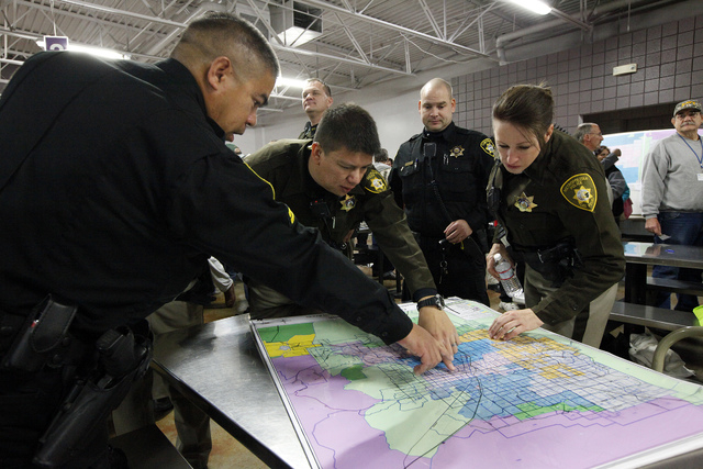 Las Vegas Police officer Aden Ocampogomez, second from left, Las Vegas Constable Randy Merrill, center, and Las Vegas Police officer Cindy Williams, right, look at a map at  Catholic Charities of  ...