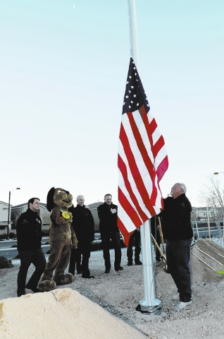 Randall Fierstein of the Providence Master Homeowners Association secures the flag Dec. 10, 2013,  during the groundbreaking ceremony for Huckleberry Park, the third park in the Providence master  ...