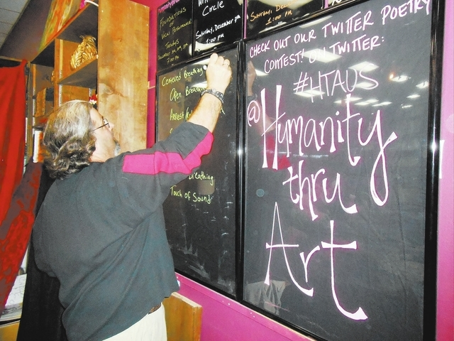 Adam Littman, founder and artistic director of Humanity Thru Art, writes on the blackboard at Dead Poet Books, 937 S. Rainbow Blvd., Dec. 3 for that night's program, Foundations of Vocal Perform ...