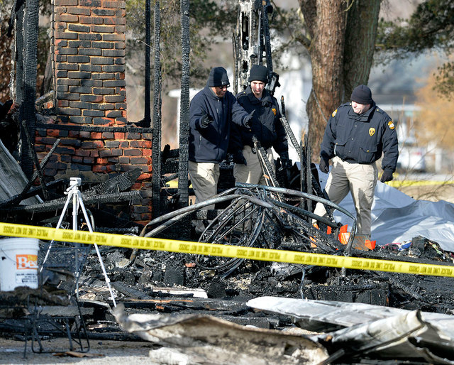 Kentucky State Fire investigators work at the scene of early morning house near Greenville, Ky., on Thursday. Nine people were killed in the fire in rural western Kentucky. Two people were taken t ...
