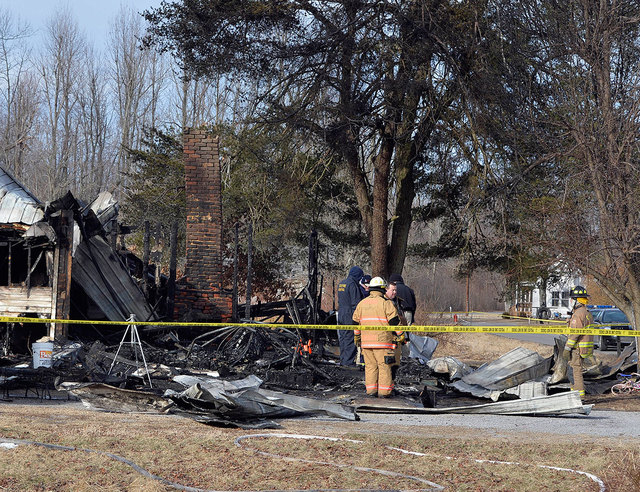 Yellow safety tape marks off the area as Kentucky State Fire investigators examine the scene of early morning house fire near Greenville, Ky., on Thursday. Nine people were killed in the fire in r ...