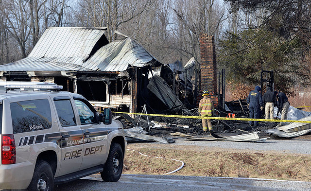 Members of the Kentucky State Fire Marshall's office look over the remains of a house fire near Greenville, Ky., Thursday. Nine people were killed in the fire in rural western Kentucky and two peo ...