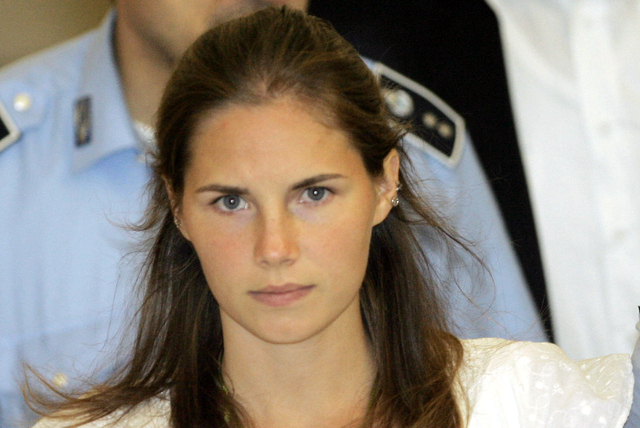 Then murder suspect Amanda Knox is escorted by Italian penitentiary police officers from Perugia's court after a hearing, central Italy on Sept. 16, 2008. (AP Photo/Antonio Calanni, File)