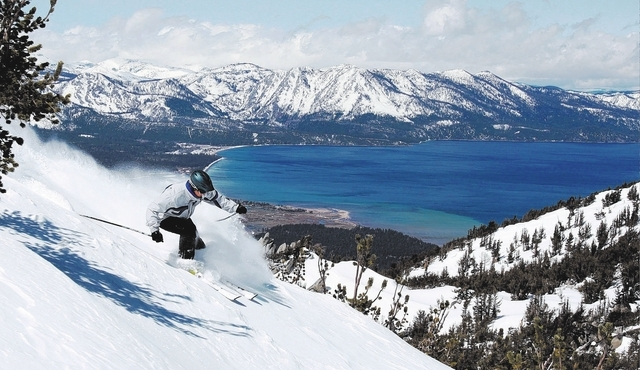 With Lake Tahoe as a backdrop, a skier kicks up some powder at Heavenly Ski Resort, Wednesday, April 14, 2010 in South Lake Tahoe, Calif.  New snow and favorable temperatures have enabled mid-wint ...