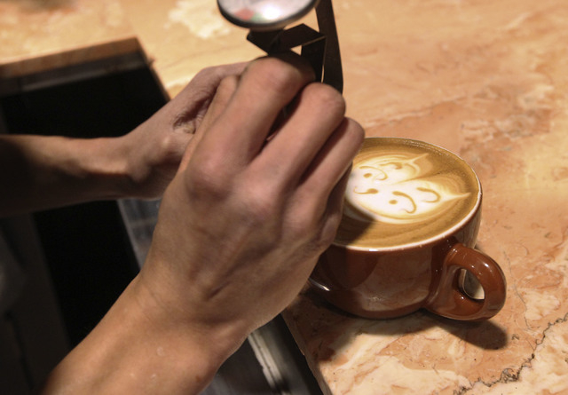 Barista Lawrence Chung creates art in cups of latte at Leone Cafe in Tivoli Village. (Jerry Henkel/Las Vegas Review-Journal)