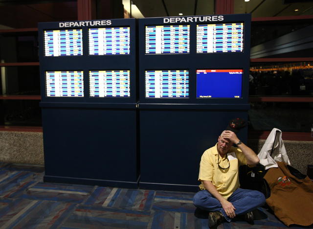 Southwest Airlines passenger Joe Holman waits for his baggage to be checked after checking in at McCarran International Airport in Las Vegas on Friday, Jan. 3, 2014. The delays are largely due to  ...