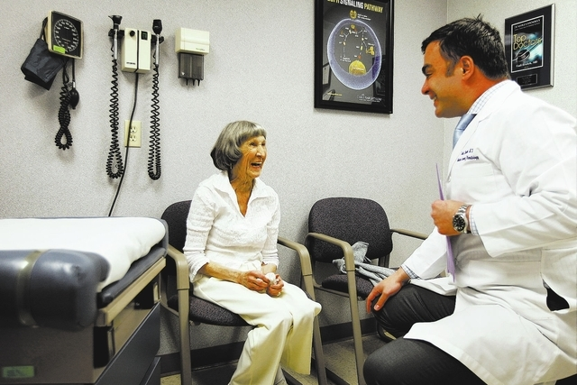 Recovering cancer patient Rosemary Rathbun, left, laughs with with her oncologist Dr. Fadi Braiteh during an examination at the Comprehensive Cancer Centers of Nevada in Las Vegas on Friday, Jan.  ...