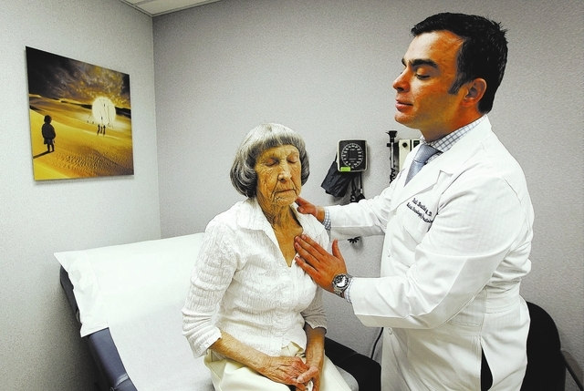 Recovering cancer patient Rosemary Rathbun, left, gets examined by her oncologist Dr. Fadi Braiteh at the Comprehensive Cancer Centers of Nevada in Las Vegas on Friday, Jan. 3, 2014. (Jason Bean/L ...