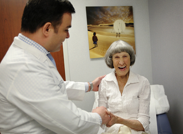 Recovering cancer patient Rosemary Rathbun, right, laughs with with her oncologist Dr. Fadi Braiteh following an examination at the Comprehensive Cancer Centers of Nevada in Las Vegas on Friday, J ...