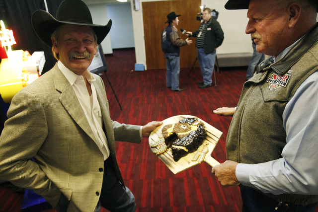 Las Vegas Convention and Visitors Authority Chairman Tom Collins, right, shows PRCA Chairman Karl Stressman a horse head cake after the LVCVA approved a deal to keep the National Finals Rodeo in L ...