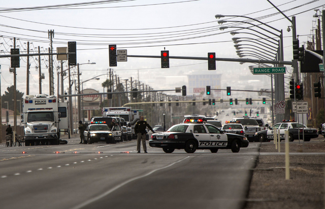 Law enforcement personnel gather outside Nellis Air Force Base at Las Vegas Boulevard and Range Road on Thursday. A man barricaded himself in the parking lot of the Mike O'Callaghan Federal Medica ...