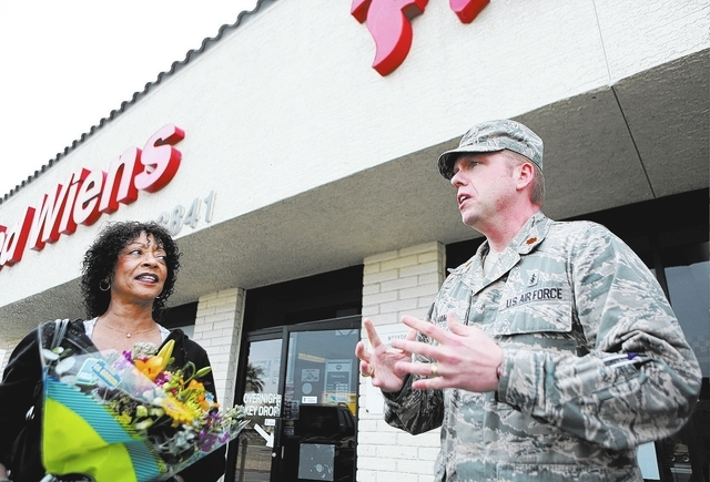 Doris Postelle, left, listens to United States Air Force Maj. Paul Hamel speak outside of Ted Wiens auto repair shop Thursday, Jan. 30, 2014, in North Las Vegas. Postelle, who holds flowers given  ...