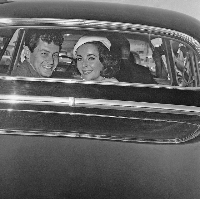 Liz Taylor and Eddie Fisher flash happy smiles through the window of their auto on May 12, 1959 in Las Vegas, as they were driven off from the county courthouse where Fisher first divorced Debbie  ...