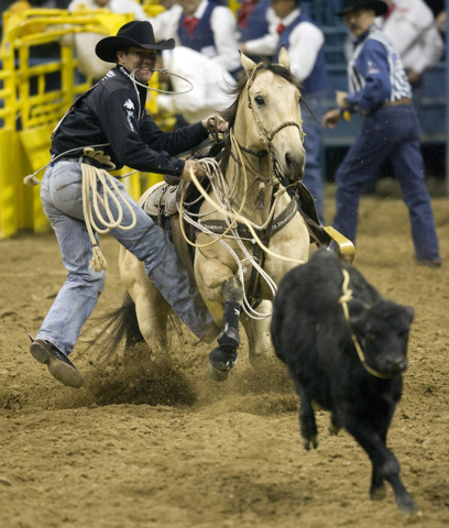 RJ FILE*** K.M. CANNON/LAS VEGAS REVIEW-JOURNAL Trevor Brazile, of Decatur, Texas, leaps from the saddle as he competes in the calf roping competition during the eighth round of the National Final ...