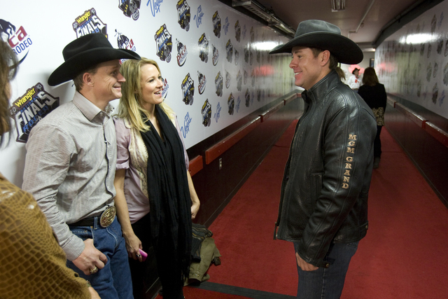 Eight-time All Around champion Trevor Brazile, right, visits seven-time All Around champion Ty Murray and his wife, recording artist Jewel, before the start of the third go-around of the National  ...