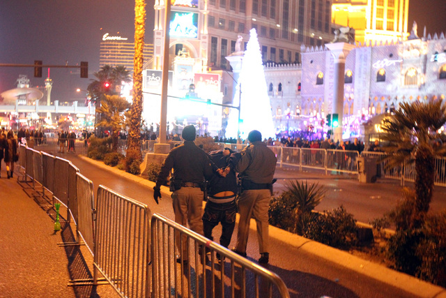 Las Vegas police arrest a reveler in front of The Venetian on the Strip on New Year's Eve Tuesday, Dec. 31, 2013. (K.M. Cannon/Las Vegas Review-Journal)