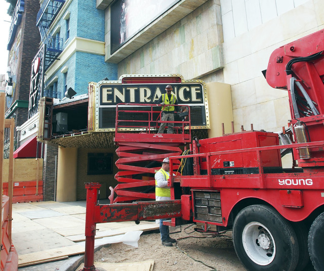 Workers quit for the day as one of the iconic New York, New York hotel-casino marquees is readied for shipment to the Neon Museum, Tuesday, Jan. 7, 2014. An entirely new facade to the hotel is pla ...
