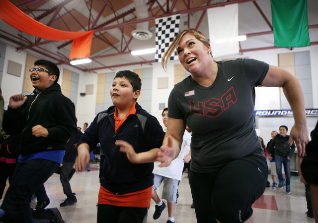 Flavio Mendoza, center, participates in a GoNoodle Ғun with US!Ӡrunning and hurdles exercise with Olympian and current American hammer throw record holder Amanda Bingson, right, during a fitness ...