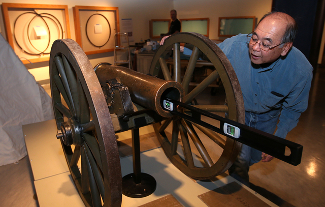 "Nevada State Museum Archaeologist Gene Hattori checks a level while setting up the Fremont Cannon as part of the ""Finding Fremont: Pathfinder of the West"" exhibit at the museum in Carson ..."
