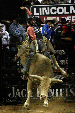 J.B. Mauney holds off Bushwacker temporarily during round six of the Professional Bull Riders World Finals Championship at the Thomas & Mack Center on Oct. 30, 2011. (Jessica Ebelhar/Las Vegas Rev ...