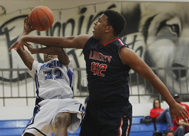 Basic's Robert Sutton (32) gets fouled by Liberty's Noah Jefferson (42) during their basketball game in Henderson on Thursday, Jan. 30, 2014. (Jason Bean/Las Vegas Review-Journal)